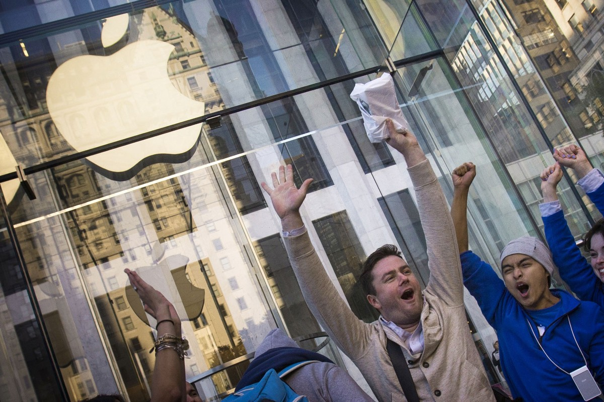 Local resident Andreas Gibson celebrates after being the first to exit the Fifth Avenue store after purchasing an iPhone 6 on the first day of sales in Manhattan, New York